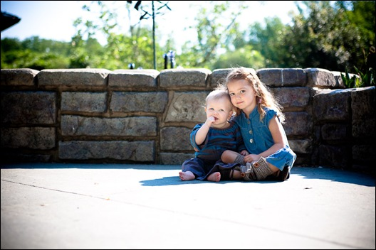 children sisters sitting in front of wall at brookside gardens in maryland