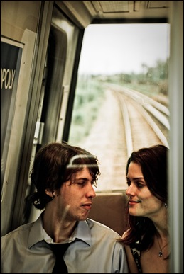 couple sitting in back of metro car with tracks in background