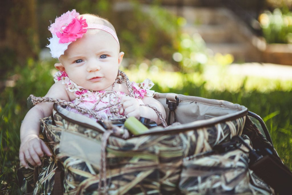A scene featuring a camouflaged hunting bag, could be seen as contrasting the flowery baby dress, or when considering the baby is in the bag, it could be seen as complementing.